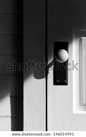 Still life of a white vintage antique door with porcelain knob and keyhole.