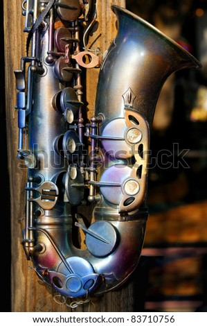 Still life of an antique saxophone hanging on a wooden pole.
