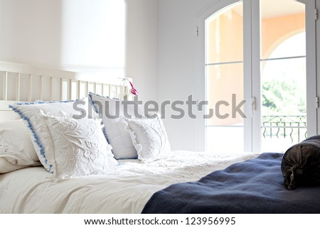 Still life of an empty bed in a hotel bedroom with patio glass doors, soft cushions and headphones. - stock photo