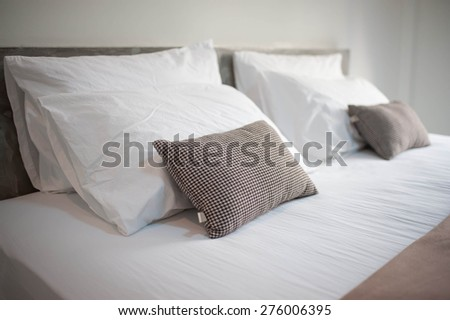 Still life of an empty bed in a hotel bedroom with soft cushions   - stock photo