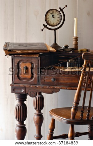 Still life of antique secretary desk from the early 1900s with vintage accessories.  Soft natural side lighting shows details including nicks and scratches from wear. - stock photo