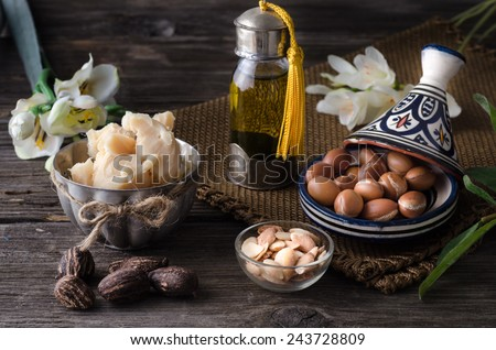 Still life of Argan oil and fruit and shea butter with nuts on a wooden table with flowers - stock photo