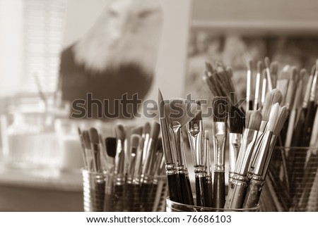 Still life of artist's brushes in studio with partially completed eagle portrait in background. (original painting by me) Closeup image in sepia tones with extremely shallow dof. - stock photo
