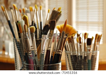 Still life of artist's brushes in sunlit studio.  Closeup with shallow dof.  Selective focus on fan brush. - stock photo