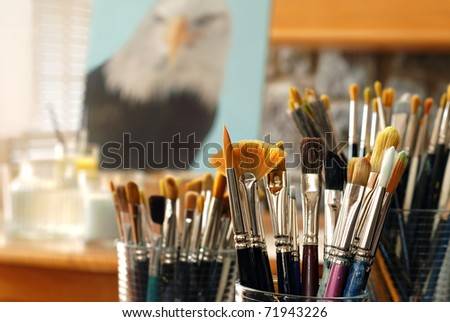 Still life of artist's brushes in sunlit studio with partially completed eagle portrait in background.  (original painting by me) Closeup with extremely shallow dof. - stock photo