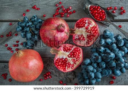 Still life of autumn fruits, pomegranates, grapes.  - stock photo