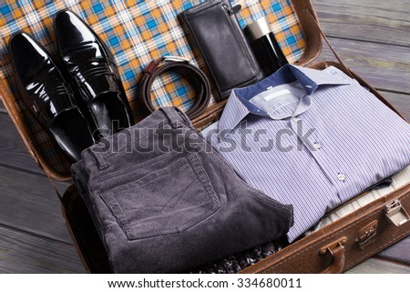 Still life of beautiful men's clothing in a retro suitcase. - stock photo