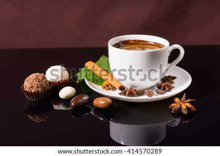 Still Life of Black Coffee Served in White Cup and Saucer with Fresh Mint Sprig, Cinnamon Stick and Star Anise, on Shiny Black Reflective Surface with Chocolate Covered Coffee Beans and Truffles - stock photo