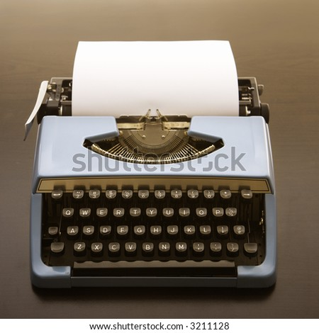 Still life of blank sheet of paper in an old fashioned typewriter. - stock photo