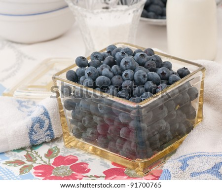 Still Life of Blueberries in a Vintage Storage Container in a Table Setting with an Old, Colorful Tablecloth and Towel. - stock photo