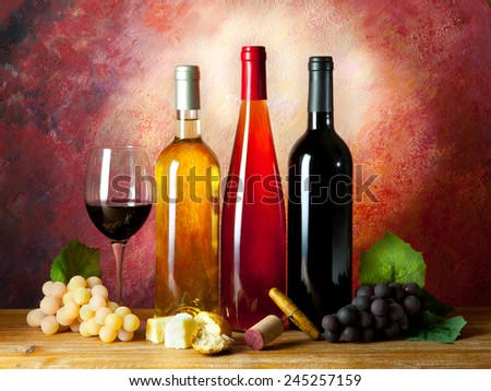 still life of bottles of wine on background of oil - stock photo