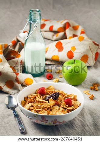 Still life of bowl of yellow crispy oatmeal cereal with raspberry and fig, green apple and glass of milk on simple linen table cloth. Rustic rural healthy breakfast meal - stock photo