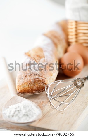 still life of bread, flour, eggs and kitchen utensil on a wooden board - stock photo