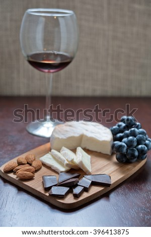 Still life of brie cheese, almonds, chocolate, grapes and wine. - stock photo