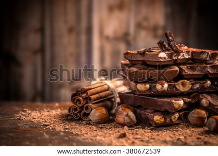 Still life of broken chocolate bar and spices on wooden table
