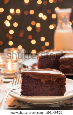 Still life of chocolate cake and a bottle of milk with blurry christmas lights. - stock photo