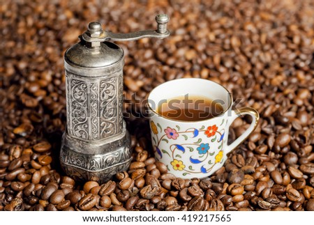 Still life of coffee beans and coffee grinder with oriental style cup of black coffee - stock photo