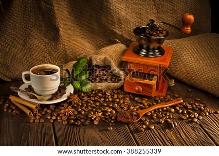 Still life of coffee beans in jute bag with coffee grinder, hot coffee cup and coffee beans on a wooden table  - stock photo