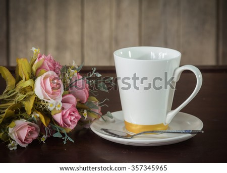 still life of coffee cup with plastic roses flowers on wood back ground in vintage sty - stock photo