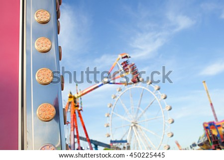 Still life of colorful fun fair festival park attractions swinging up with energy and motion blur against a blue sky, outdoor activities. Bright lights rollercoaster rides, recreational exterior.