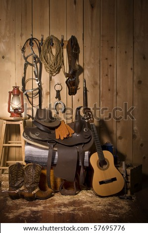 Still life of cowboy paraphernalia in the tack room of a barn - stock photo