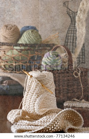 Still life of crochet thread and baskets of knitting yarn with partially finished needlework projects.  Photo layered with texture for artistic effect. - stock photo