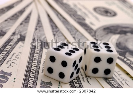 Still-life of dollars with playing bones on white background - stock photo