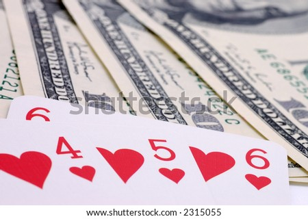 Still-life of dollars with playing cards on white background - stock photo