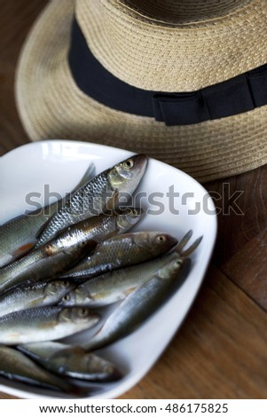 Still life of fishes and hat on a wooden table