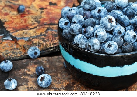 Still life of fresh picked organic blueberries on a rustic slate background. - stock photo