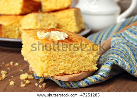 Still life of freshly baked homemade cornbread with butter melting on top.  Close-up with shallow dof. - stock photo