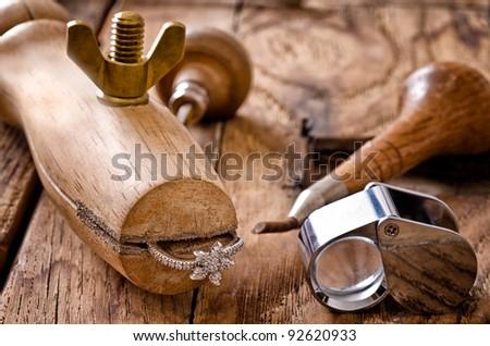 Still life of goldsmith's tools with diamonds ring - stock photo