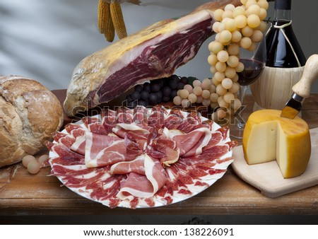 still life of ham, cheese and wine grapes - stock photo