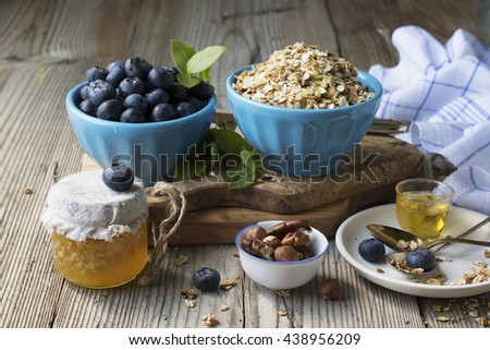 Still life of healthy breakfast. Cereal flakes for cereal, blueberry ripe berries, fresh flower honey, nuts on a cutting board from olive wood are served with table linens in a cage. selective focus - stock photo