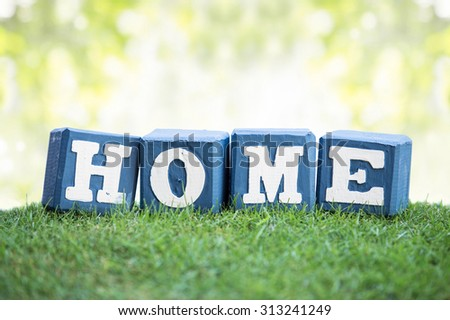 still life of HOME sign concept made of wooden blocks on a green grass with bokeh background - stock photo