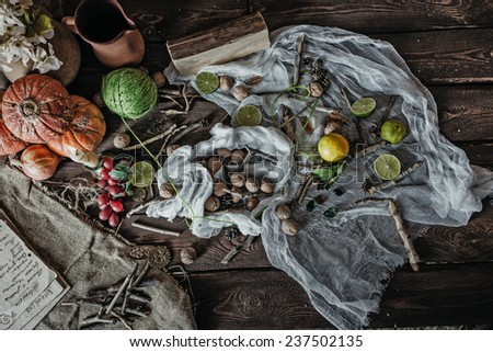 Still life of ingredients for making potions witch. Nuts, sticks, scrolls, thread, runes, charms, pumpkin, lime, lemon, pine cones and other ingredients lie on a wooden table. - stock photo