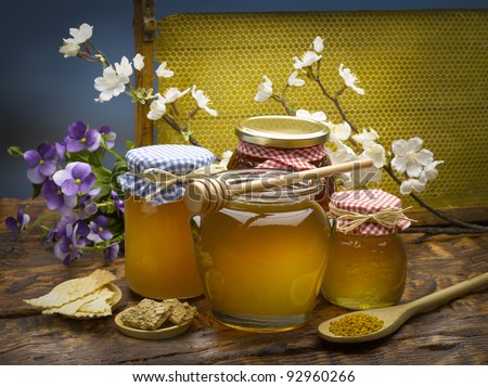 still life of jars of honey and pollen with a spoon. - stock photo