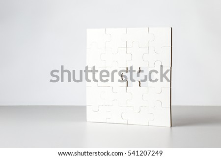 still life of jigsaw puzzle with piece missing standing on white background