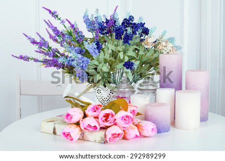 Still life of lavender flower tulips, candles and a book on light background - stock photo