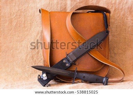 Still life of Military bayonet knife and leather bag on sack background