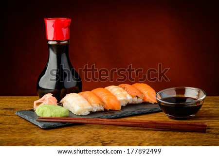 still life of mixed plate with nigiri sushi, soy sauce and chopsticks - stock photo