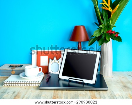 Still life of modern colorful interior workspace with laptop, tablet, flower vase - stock photo