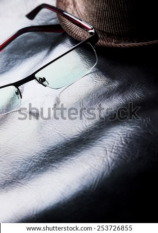 Still life of modern eyeglasses with brown corduroy Fedora hat against black leather. - stock photo