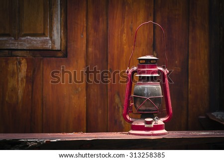 Still life of old hurricane lamp on wooden background