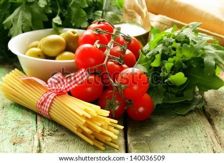 still life of  olives,  herbs, cherry tomatoes and Italian pasta - stock photo