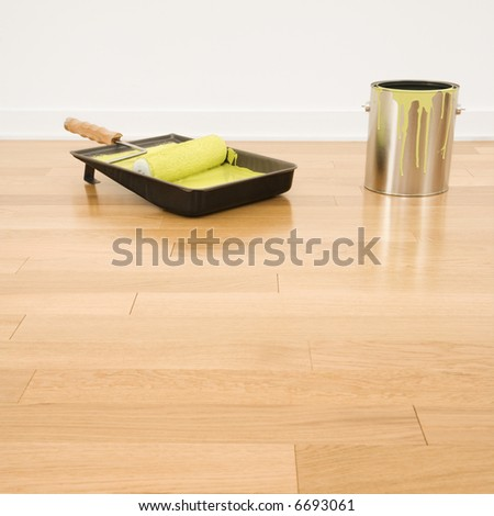 Still life of paint roller in tray with paint can on wood floor.