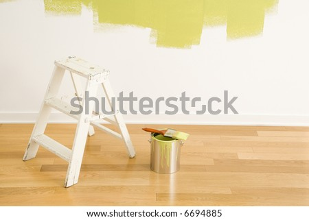 Still life of paintbrush on paint can with stepladder painted wall.