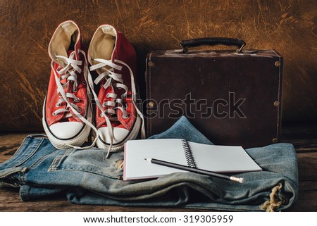 still life of pair of jeans and red sneakers,pencil and note book on wooden floor with leather background