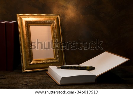 still life of picture frame on table with diary book. - stock photo