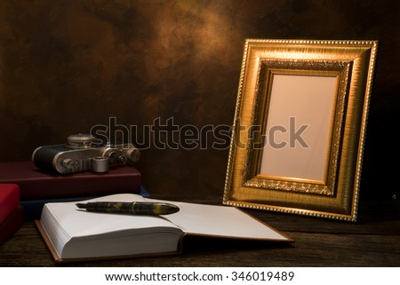 Still life of picture frame on table with vintage camera and diary book. - stock photo